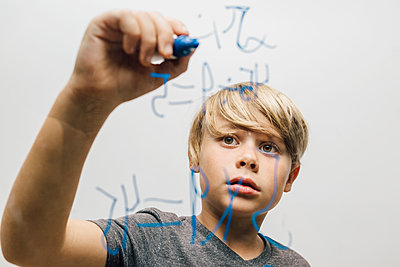 Close up of boy's hand writing equation onto glass wall - p429m1504962 by JFCreatives