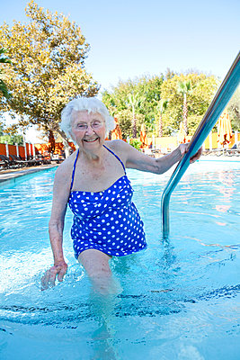 Older Caucasian woman walking in swimming pool - p555m1408860 by Shestock
