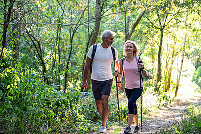 Smiling mature couple hiking together in forest - p623m2271768 by Frederic Cirou