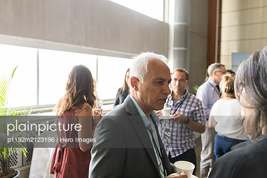 Business people talking, networking during conference coffee break - p1192m2123196 by Hero Images
