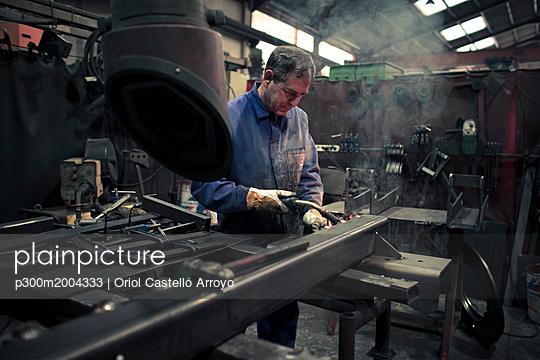 Welder welding metal in a factory - p300m2004333 von Oriol Castelló Arroyo