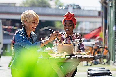 Happy young women friends enjoying dim sum lunch at sunny sidewalk cafe - p1023m2066216 by Tom Merton
