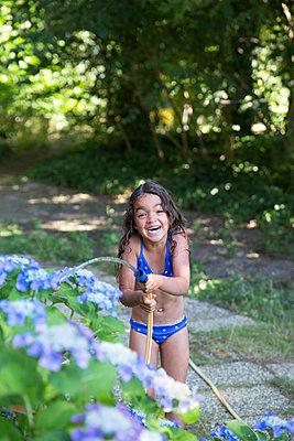 Mädchen spielt mit einem Gartenschlauch - p1231m2013520 von Iris Loonen