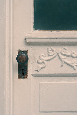 Close up of old fashioned Doorknob on Carved White Front Door - p1617m2264075 by Barb McKinney