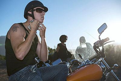Man on motorcycle tying helmet strap - p300m1019297f by zerocreatives