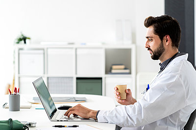Male doctor using laptop while sitting at desk in hospital - p300m2274646 by Giorgio Fochesato
