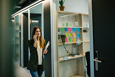 Thoughtful female entrepreneur talking on smart phone in corridor at office - p300m2277758 by Xavier Lorenzo