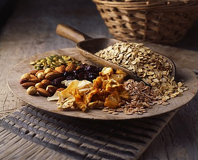 Dried fruits, nuts and oats on wooden plate - p429m1106740f by Diana Miller
