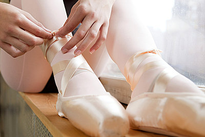 Girl tying ballet shoes - p9245527f by Image Source