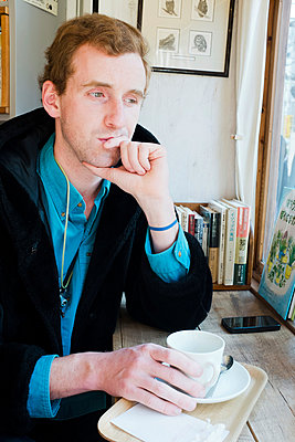 Young man with coffee cup - p956m1044302 by Anna Quinn