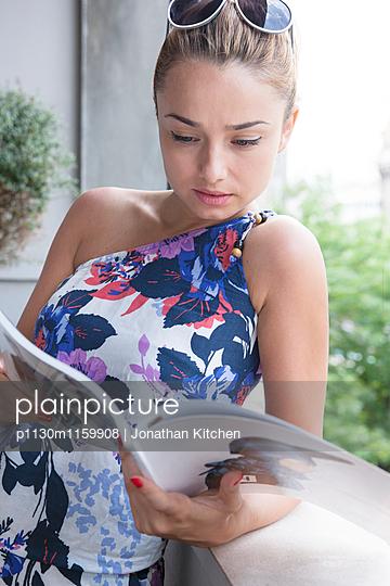 Junge Frau liest in einer Zeitschrift - p1130m1159908 von Jonathan Kitchen