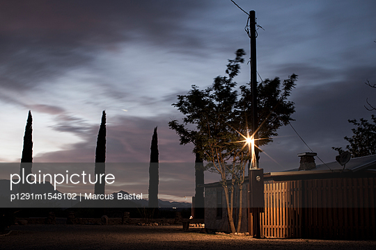 Sunset Behind Mountains With A Wooden Electricity Pylon Light And Electricity Box Attached To It In Front Of A Small Low Building And Tree Surrounded By Wooden Fencing - p1291m1548102 by Marcus Bastel