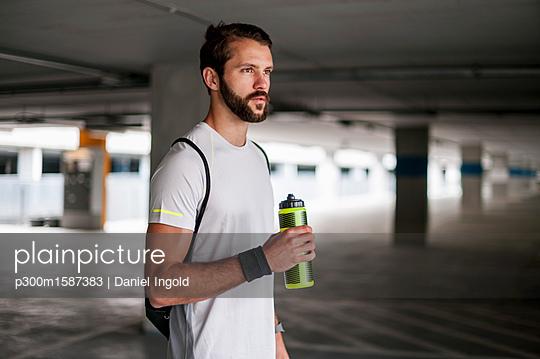 Athlete in parking garage holding drinking bottle - p300m1587383 von Daniel Ingold
