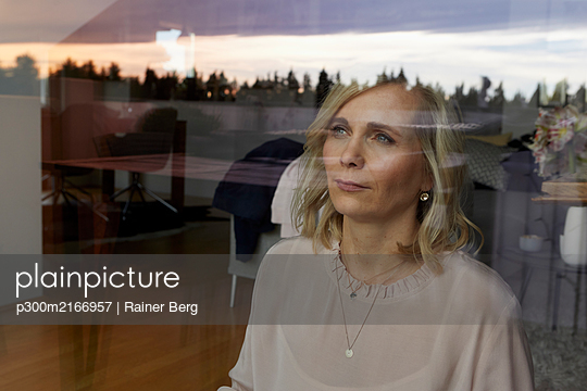 Portrait of blond woman behind windowpane at home - p300m2166957 by Rainer Berg