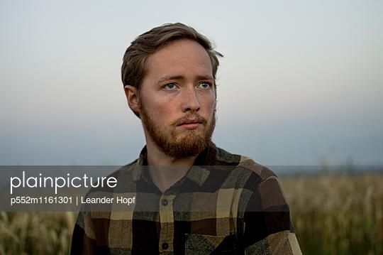 Porträt eines jungen Mannes auf dem Land - p552m1161301 von Leander Hopf