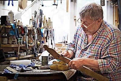 Craftsman shaping fretboard in workshop - p1166m1163576 by Cavan Images