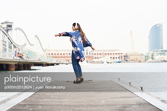 Spain, Barcelona, happy young woman with headphones dancing on jetty - p300m2012624 von Juan Novakosky