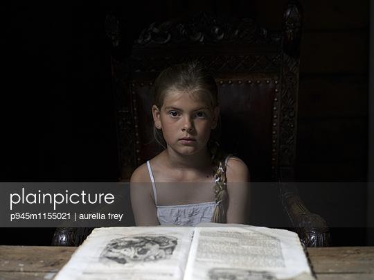 Mädchen sitzt vor einem Tisch mit Märchenbuch - p945m1155021 von aurelia frey