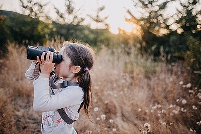 Side view of girl looking through binoculars while standing on field - p1166m1534208 by Cavan Images
