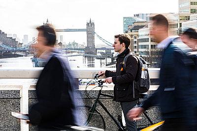 UK, London, businessman pushing  bicycle in the city - p300m1581404 von William Perugini