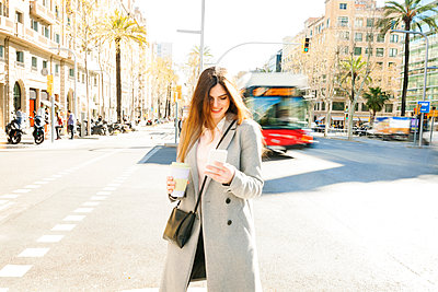 Spain, Barcelona, smiling young woman with coffee to go standing at roadside looking at cell phone - p300m1587181 by Valentina Barreto