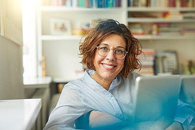 Portrait of content mature woman with tablet at home - p300m1587857 von Philipp Nemenz