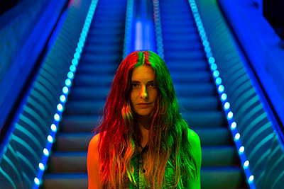 Portrait of illuminated young woman in front of blue lighted escalator - p300m2028725 by VITTA GALLERY