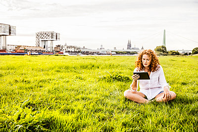 Germany, Cologne, young woman sitting on meadow looking at tablet - p300m2069821 by Jo Kirchherr