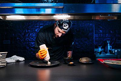 Chef preparing a dish in restaurant kitchen - p300m2166737 by Daniel González