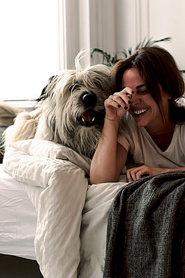 Laughing mature woman lying on bed playing with her dog - p300m2188490 by Eloisa Ramos
