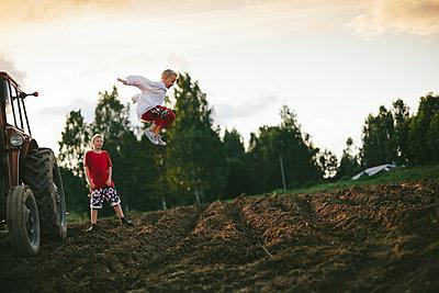 Boy jumping on field - p312m2091524 by Matilda Holmqvist