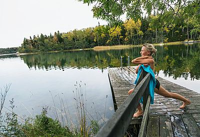 Woman on jetty - p312m2101673 by Pernille Tofte