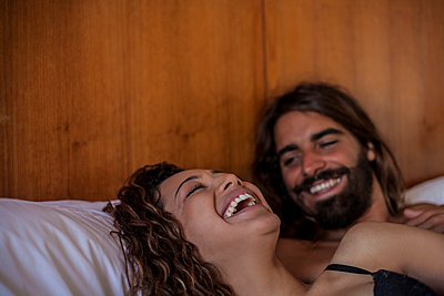 Young couple lying in bed laughing, head and shoulders - p429m2019014 by Seb Oliver