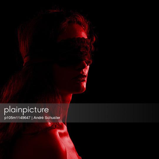 Junge Frau mit verbundenen Augen im roten Licht - p105m1149647 von André Schuster