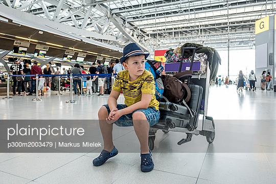 Thailand, Bangkok, portrait of boy waiting on baggage cart at airport - p300m2003479 von Markus Mielek