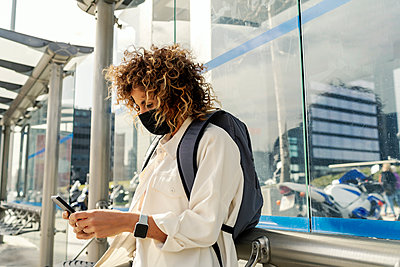 beautiful woman waiting for the bus while looking at her smartphone - p1166m2255047 by Cavan Images