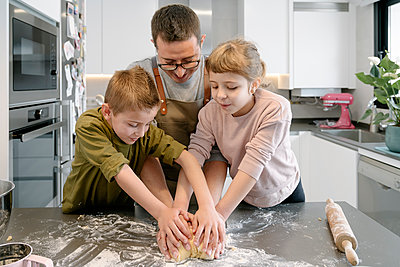 Children helping man while kneading dough in kitchen - p300m2273577 by Albert Martínez