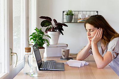 Tired woman with head resting in arms at home office - p300m2287186 by VITTA GALLERY