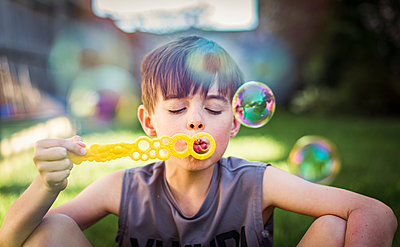 Young boy blowing bubbles outdoors on a summer day. - p1166m2138080 by Cavan Images