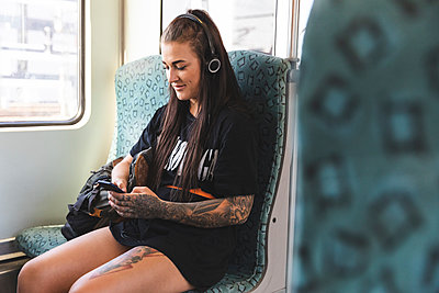 Tattooed young woman sitting in commuter line using smartphone and headphones, Berlin, Germany - p300m2156862 von William Perugini