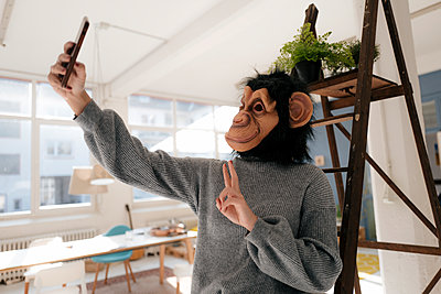 Young woman with monkey mask takes a selfie - p586m2021370 by Kniel Synnatzschke