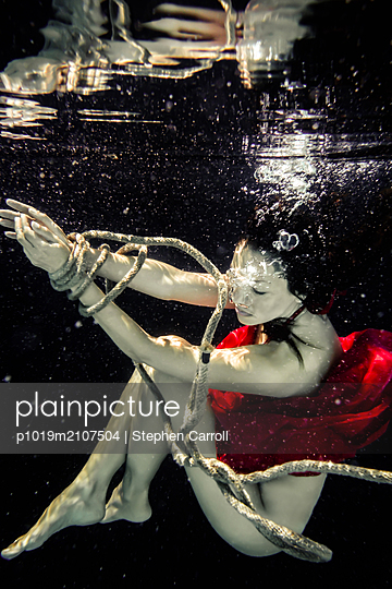 Woman Tied Up with Rope Drowning Under Water  - p1019m2107504 by Stephen Carroll