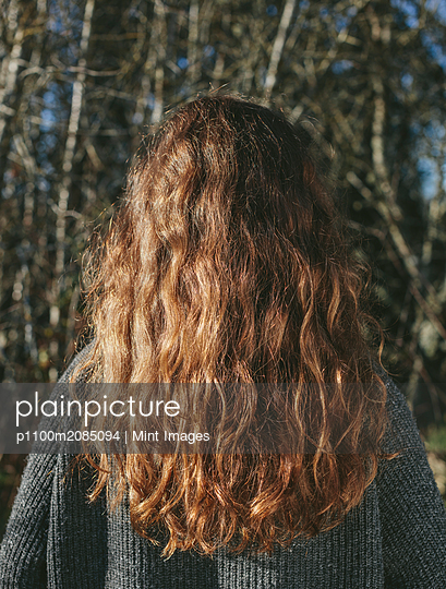 View from behind of teenage girl with long, wavy, brown hair - p1100m2085094 by Mint Images