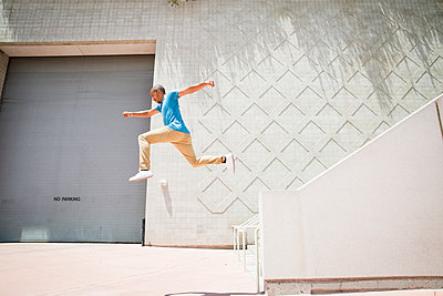 Young man jumping in the air down a stairway. - p1100m1038923 by Mint Images