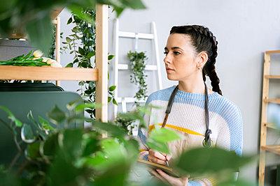 Young woman working in a gardening laboratory or plant shop - p300m2275362 von Giorgio Fochesato