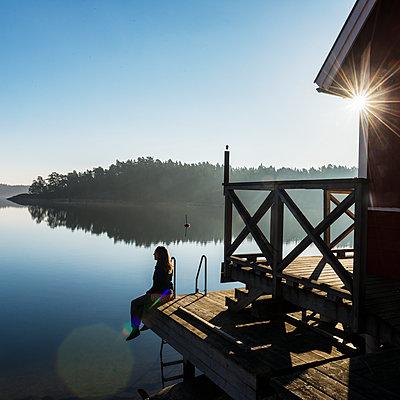 Woman sitting at lake - p312m1472424 by Fredrik Schlyter