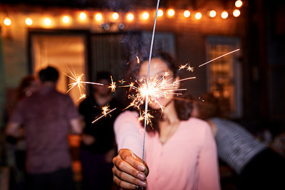 Smiling Mixed Race woman holding burning sparkler at backyard party - p555m1303239 by Granger Wootz