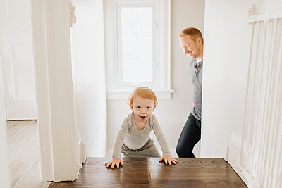 Father following son crawling up stairway in house - p924m2153082 by Sara Monika
