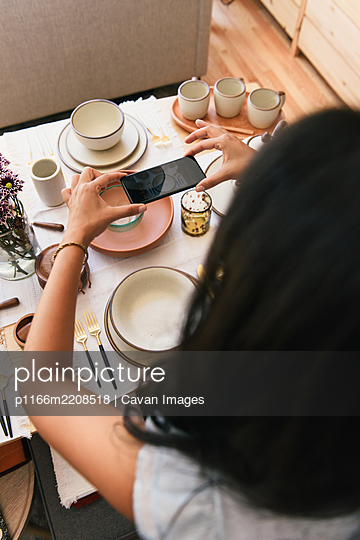Woman capturing phone photo from overhead of dinnerware display - p1166m2208518 by Cavan Images