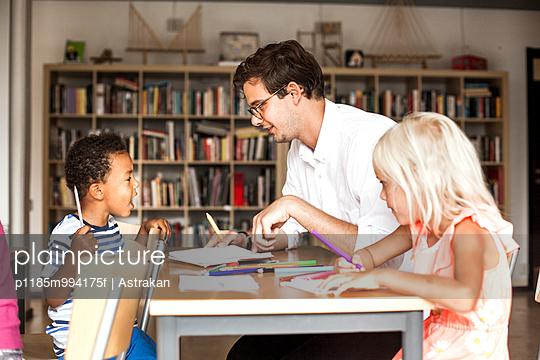 Male teacher teaching students during art class